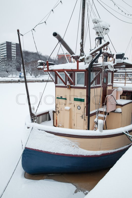 Stock image of 'Small boat moored near river coast. Winter in Turku town, Finland'