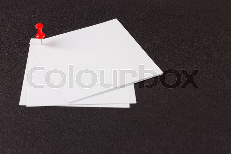 Stock image of 'white sticker attached drawing pin on the black background'