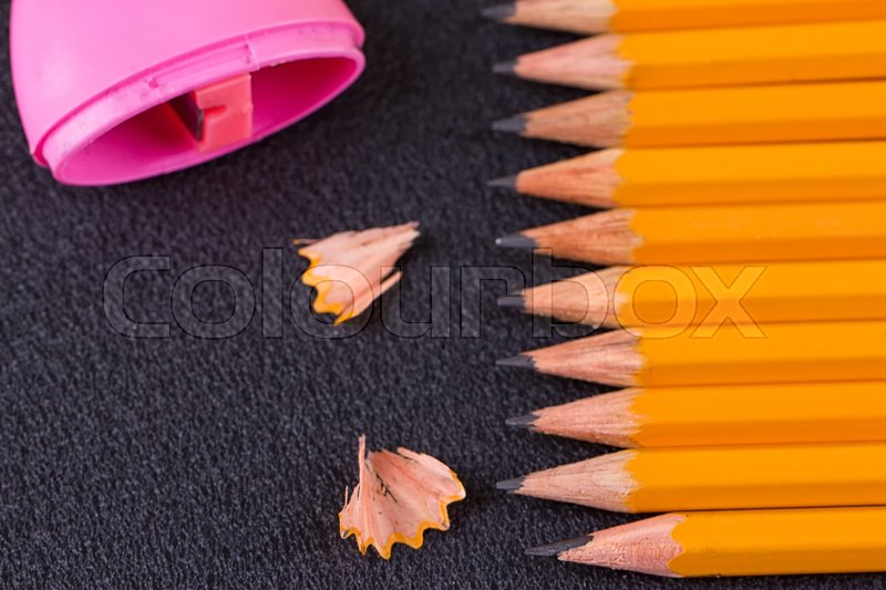 Stock image of 'Simple pencils and a pink pencil sharpener on a black background'