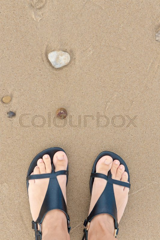 Stock image of 'female feet seen from above standing in the sand with small stones in front. vibrance added'