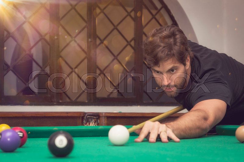 Stock image of 'Man playing billiards in a pool table.'