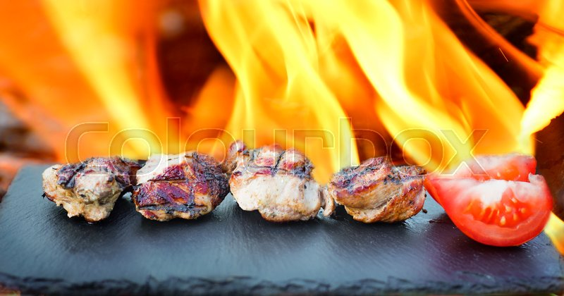 Stock image of 'Meat cooked lies on a black stone with a shallow depth of field'