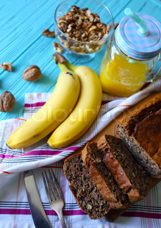 Stock image of 'Healthy eating. Banana bread, bananas and orange juice on the table '