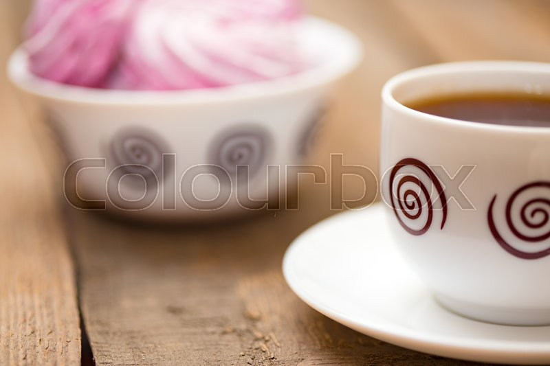 Stock image of 'fruit marshmallows and the cup of tea on a wooden background '