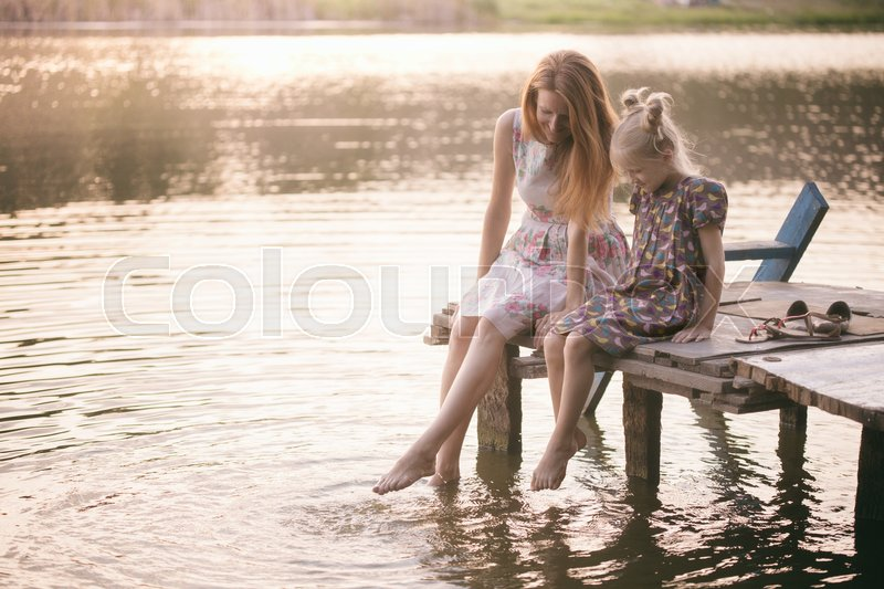 Stock image of 'smiling mother and daughter sitting on the pier warm autumn day dangling his legs in the water at the sunset '