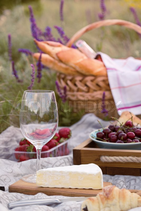 Stock image of 'Summer - picnic in the meadow. Cheese brie, baguette, strawberry, cherry, wine, croissants and basket '