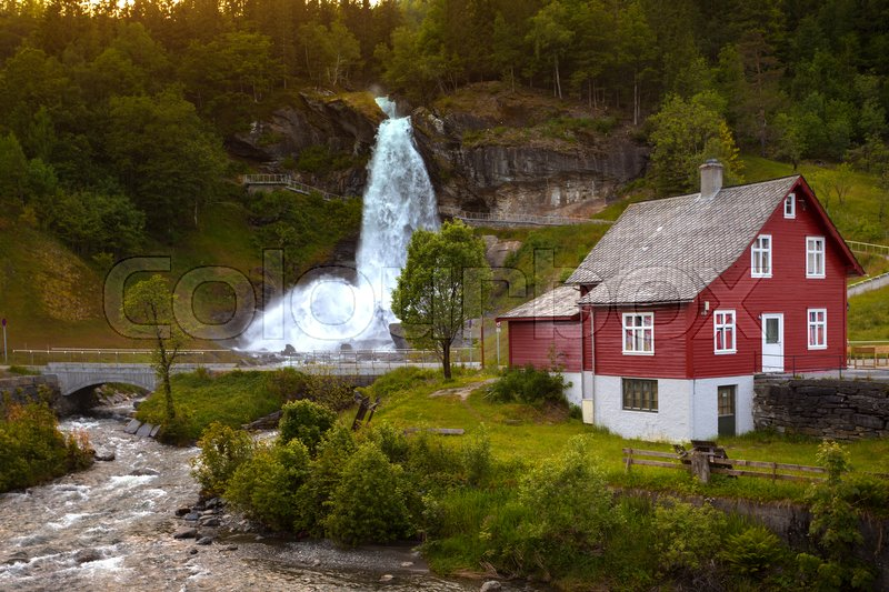 Stock image of 'traditional norwegian red wooden house and steinsdalsfossen waterfall in the background, norway '
