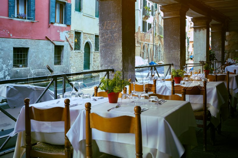 Stock image of 'cafe. tables and chairs  at the ancient streets and canals of Venice Italy '
