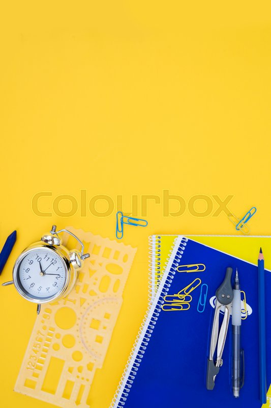 Stock image of 'back to school styed scene with blue and yellow school supplies on yellow background'