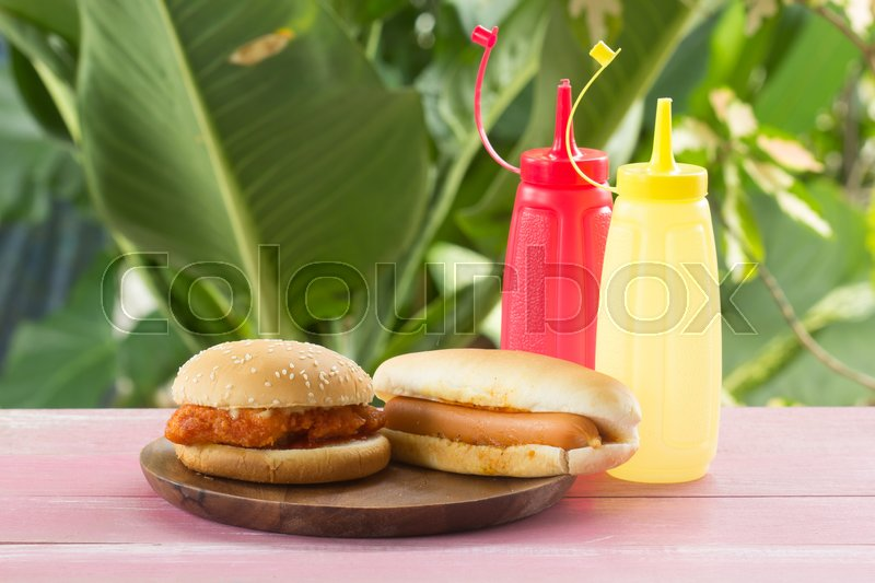 Stock image of 'Hot dogs and  chicken burgers on the wooden plate'