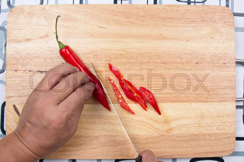 Stock image of 'Hand cutting Hot Chili Peppers on wooden broad / Cooking green curry concept'