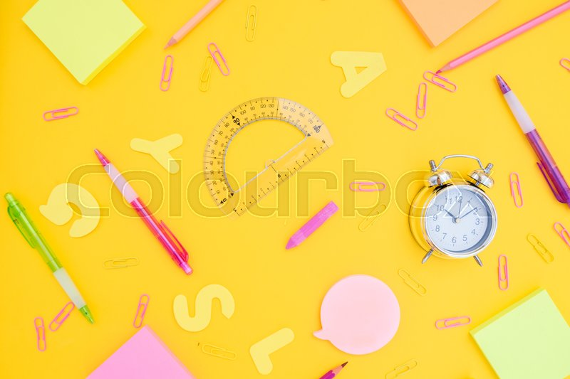 Stock image of 'back to school or office styed pattern with multicolored school supplies on yellow'