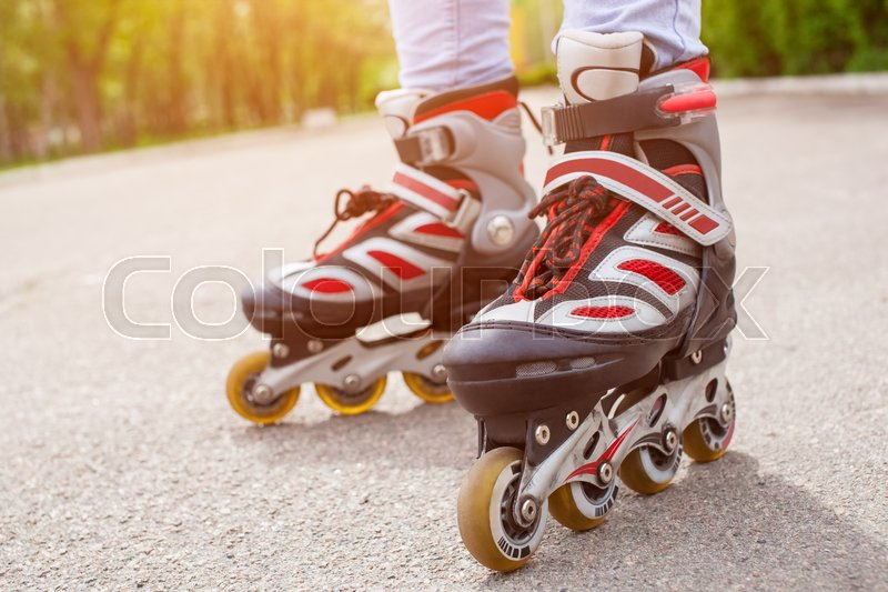 Stock image of 'Girl teenager rollerblading on the asphalt in the park, legs close-up'