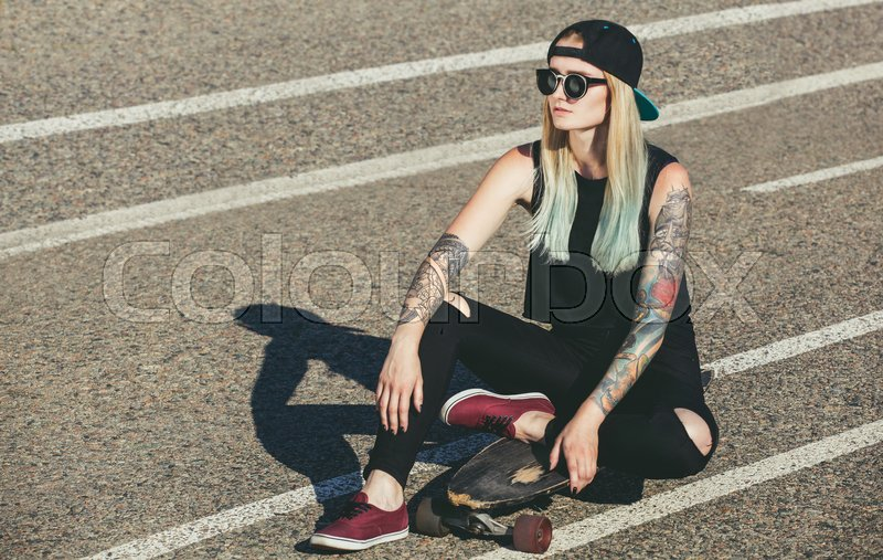 Stock image of 'A beautiful, sexy hipster blonde with blue hair in tattoo sits on a longboard  with glasses and a cap on the asphalt on the street'