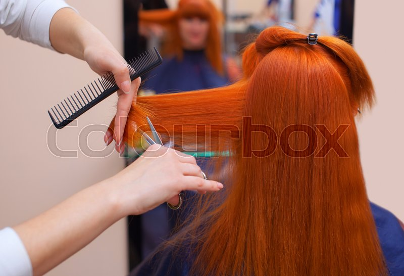 Stock image of 'The hairdresser does a haircut with scissors of hair to a young with red hair girl in a beauty salon.'