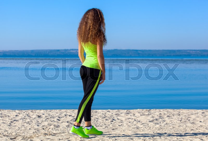 Stock image of 'Young athlete with curly hair, light green tracksuit and sneakers running on the beach in summer, morning exercise. Sports and healthy lifestyle.'