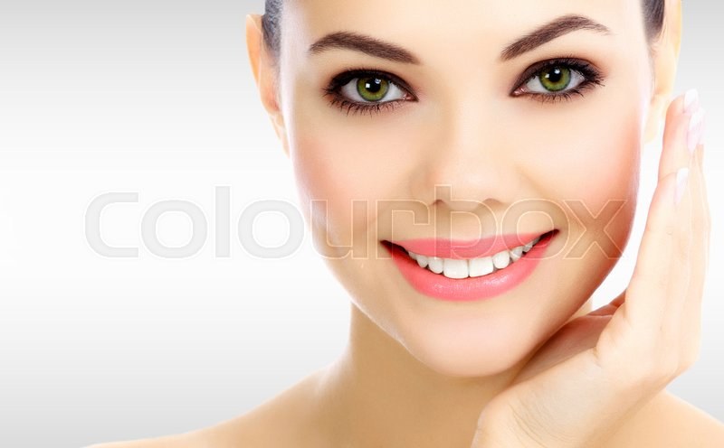 Stock image of 'Face of pretty woman against a grey background with copyspace'