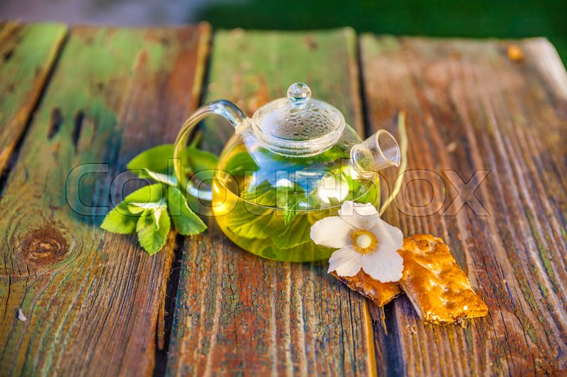 Stock image of 'Tea pot of herbal tea on a wooden table.'
