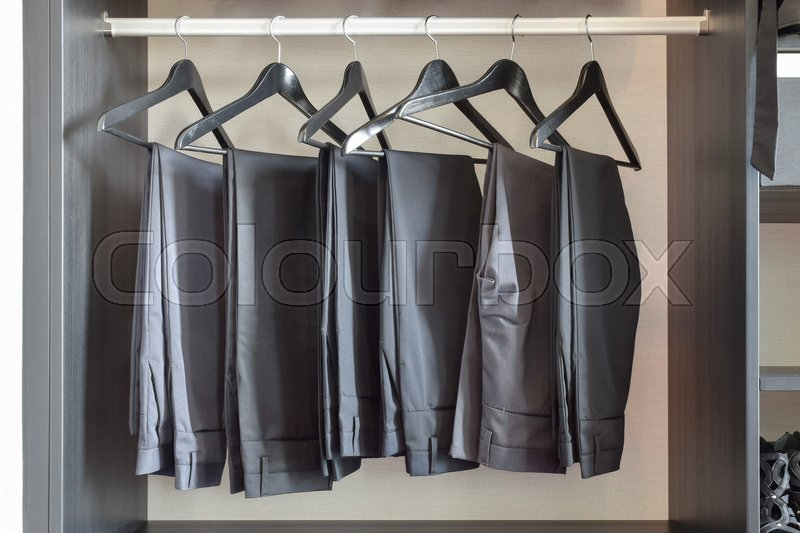 Stock image of 'Row of black pants hangs in wardrobe at home'