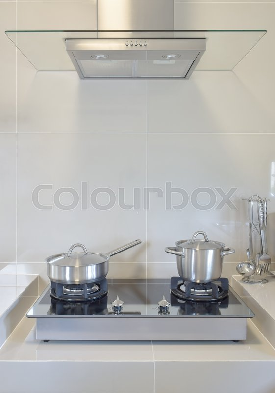 Stock image of 'Stainless pan on gas stove with utensil in modern kitchen'