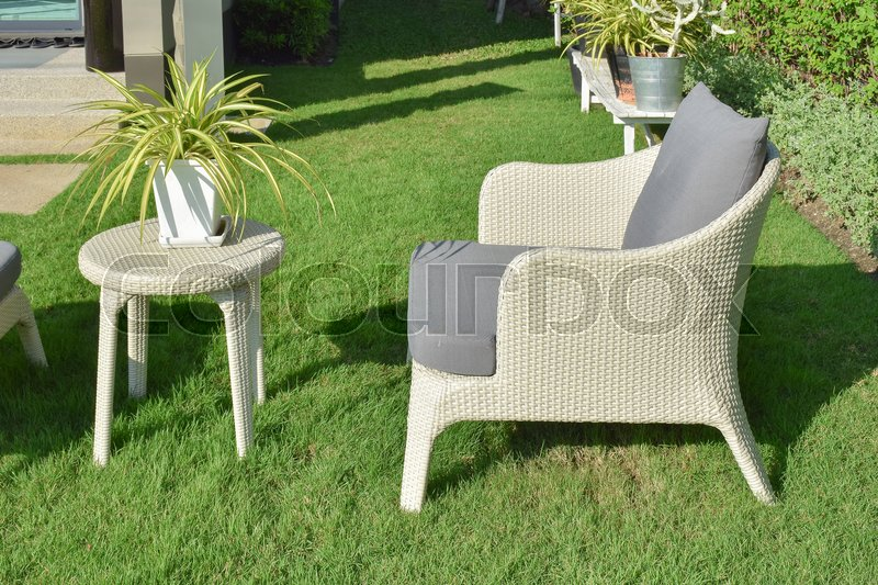 Stock image of 'Green garden with an outdoor furniture lounge group with rattan chairs, sofa and table'
