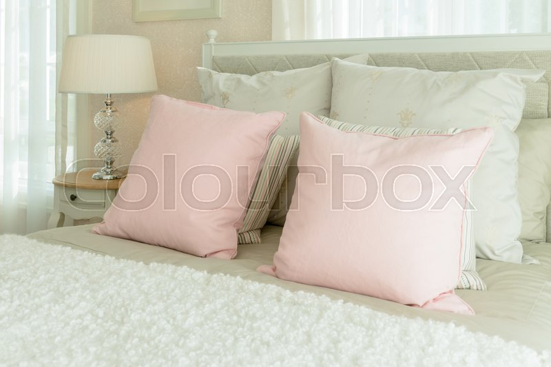Stock image of 'Luxury bedroom interior with pink pillows and reading lamp on bedside table'