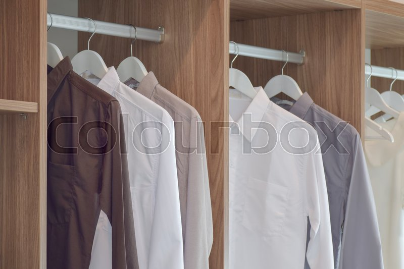 Stock image of 'Classic color shirts hanging in wooden wardrobe'