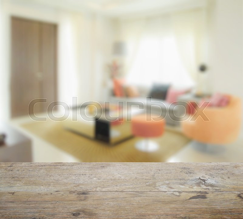 Stock image of 'Wooden table top with blur of modern living room interior with orange tone decoration'