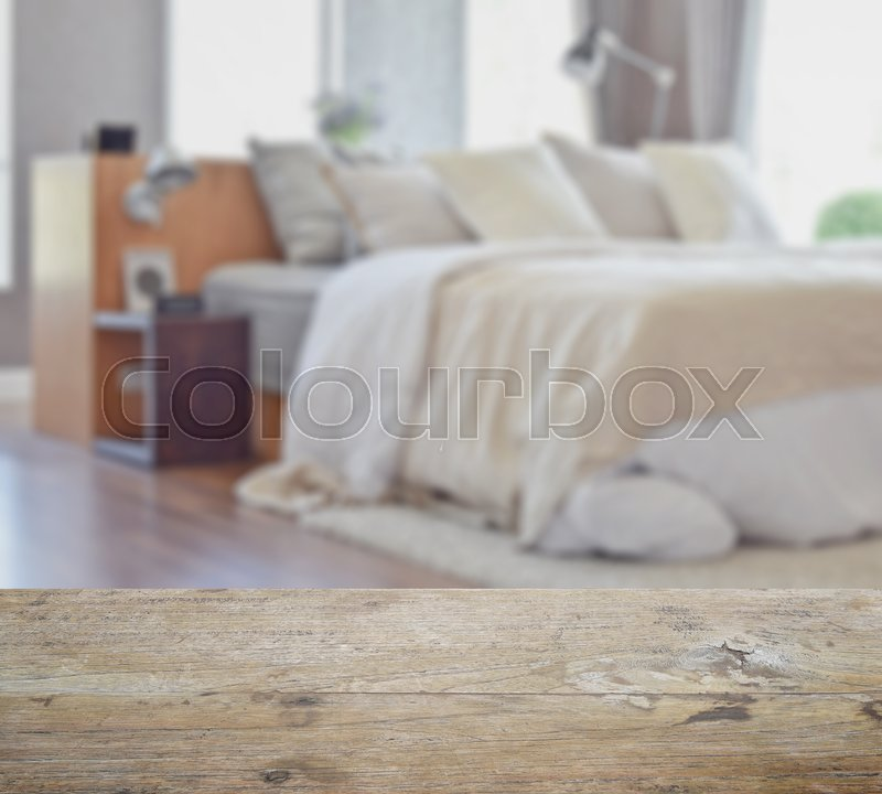 Stock image of 'Wooden table top with blur of modern bedroom interior design with white pillows on bed'