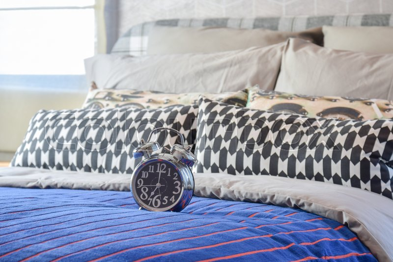 Stock image of 'Decorative alarm clock with black and white pillows on bed in modern bedroom'