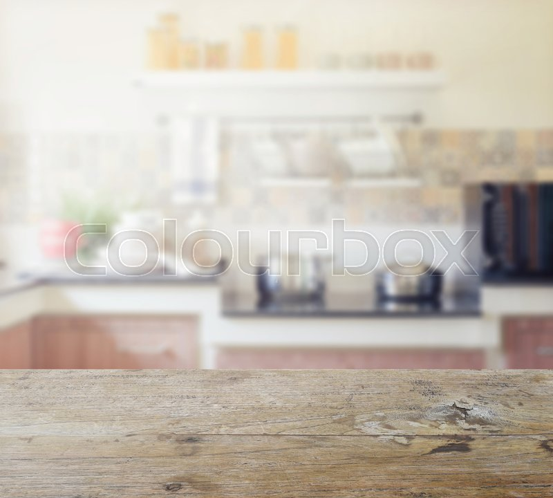 Stock image of 'Wooden table top with blur of modern kitchen interior for background'