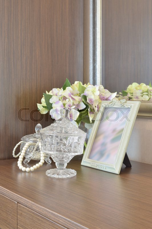 Stock image of 'Jewelry crystal jar with picture frame and flowers on the wooden table'