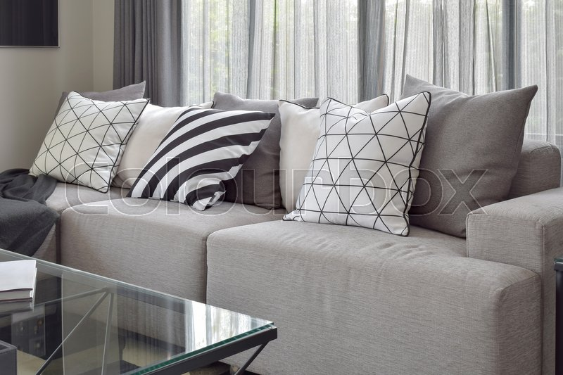 Stock image of 'Light gray sofa with varies pattern pillows in modern living corner'