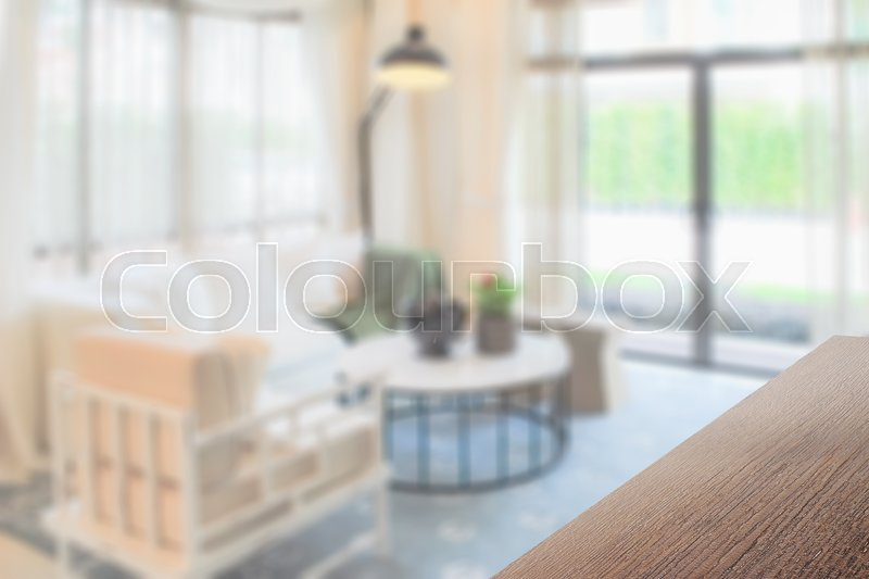 Stock image of 'wooden table top with blurred background interior living room with decorative lamp'