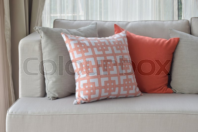 Stock image of 'Chinese pattern in orange with deep orange and gray pillows on light gray sofa set'