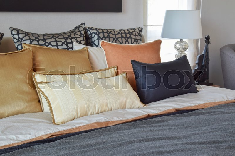 Stock image of 'Modern bedroom interior with orange and gold pillows on bed and bedside table lamp'