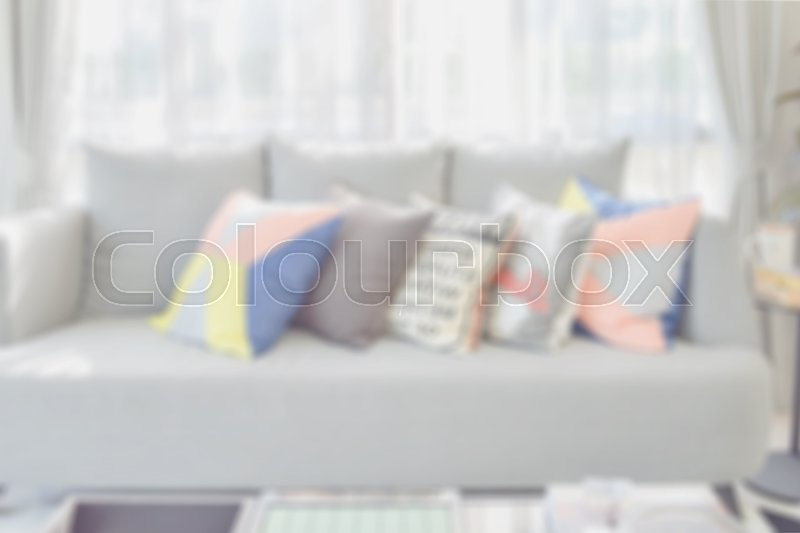 Stock image of 'Blur image of modern living room design with colorful pillows on sofa for background'