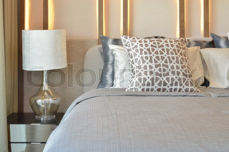 Stock image of 'Stylish bedroom interior design with brown pillows on bed and decorative table lamp.'