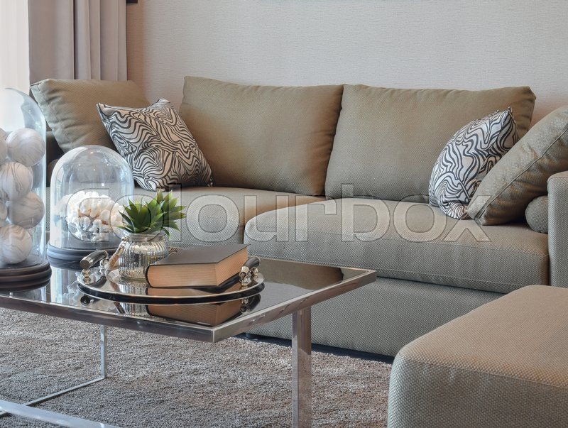 Stock image of 'Comfortable velvet sofa with grey striped pillows in modern living room'