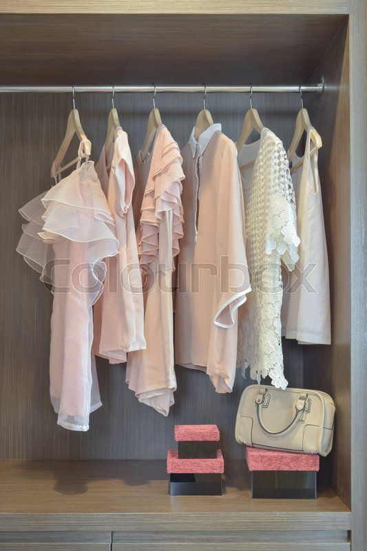 Stock image of 'Sweet pastel blouses are hanging in open wooden wardrobe'