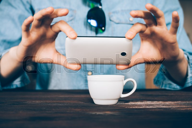 Stock image of 'Woman in a denim shirt takes a picture of a cup of coffee at a cafe, close-up'