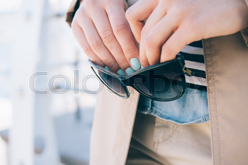 Stock image of 'Woman in a beige coat holds sun glasses in her hands close-up'
