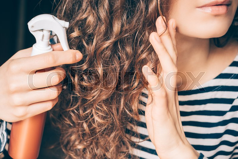Stock image of 'Woman applying spray on curly brown hair close-up'