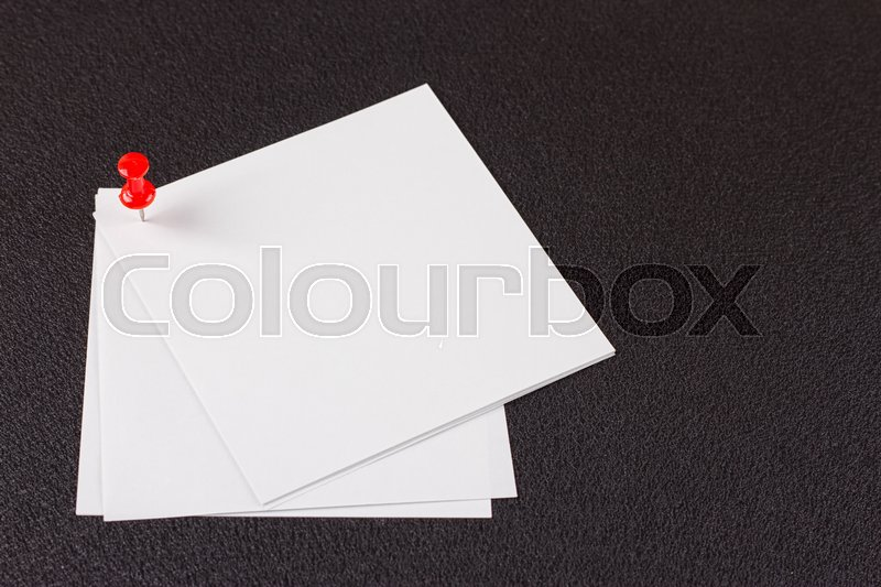 Stock image of 'Note paper with red pin, on black. Clipping path included'