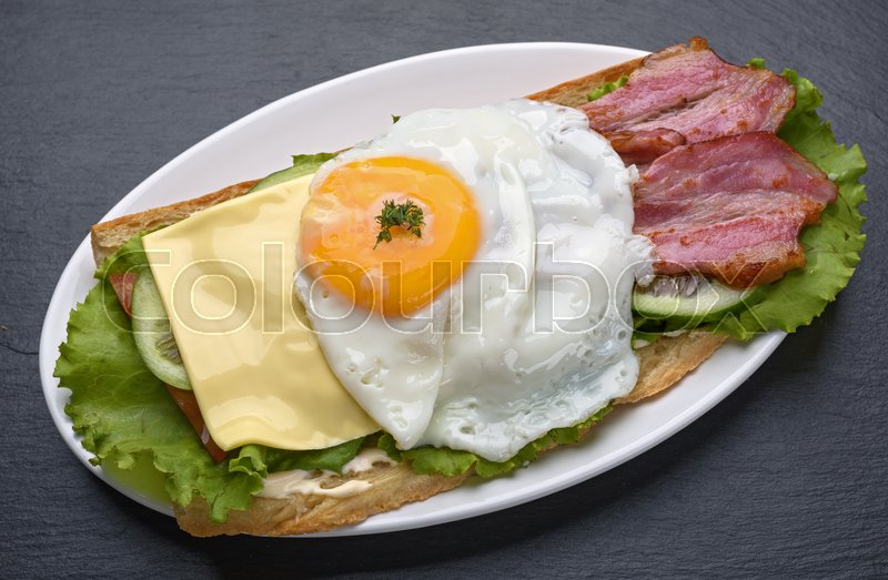 Stock image of 'Sandwich with fried egg on a dark stone background'