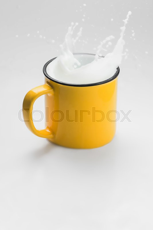 Stock image of 'Yellow cup of fresh milk splash wth drops on white background'