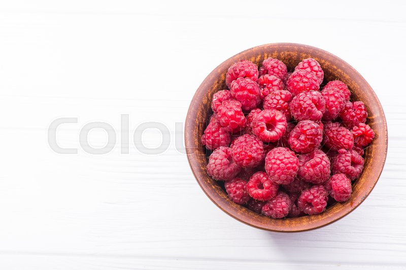 Stock image of 'Red fresh raspberry in bowl on wooden table'