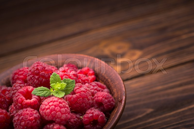 Stock image of 'Red fresh raspberries on rustic wood table'