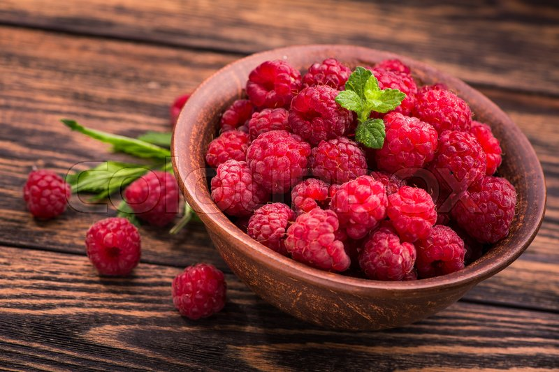 Stock image of 'Summer ripe fruit iin bowl. old wooden table at background. raspberry dessert'