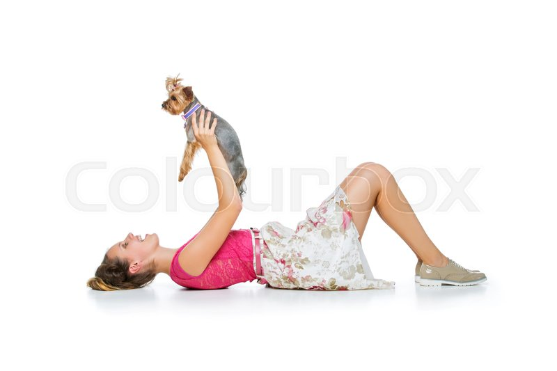 Stock image of 'Beautiful young teenage girl in top and skirt holding small cute yorkshire terrier dog. Copy space. Studio shot on light background.'